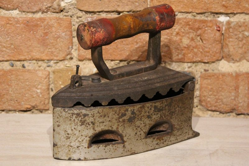 Old iron with red wooden handle