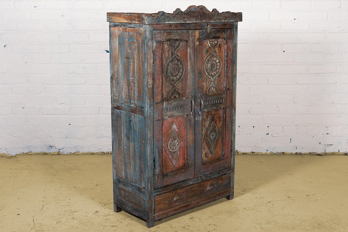 Old wooden cupboard with aged blue and red paint