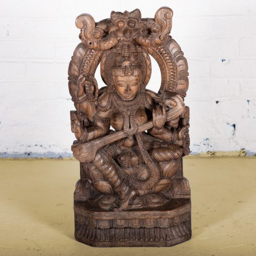 Intricately hand-carved wooden statue of Saraswati